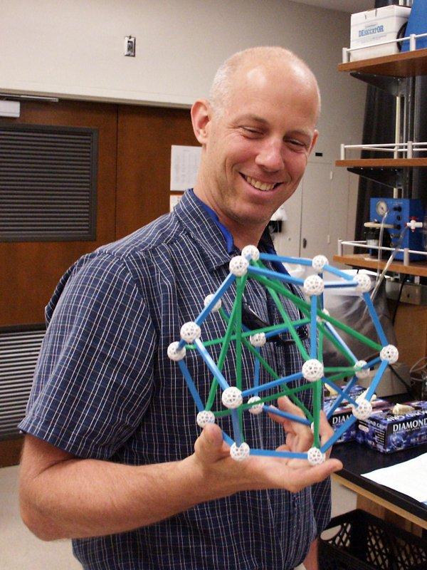 A man holds a plastic molecular model in lab