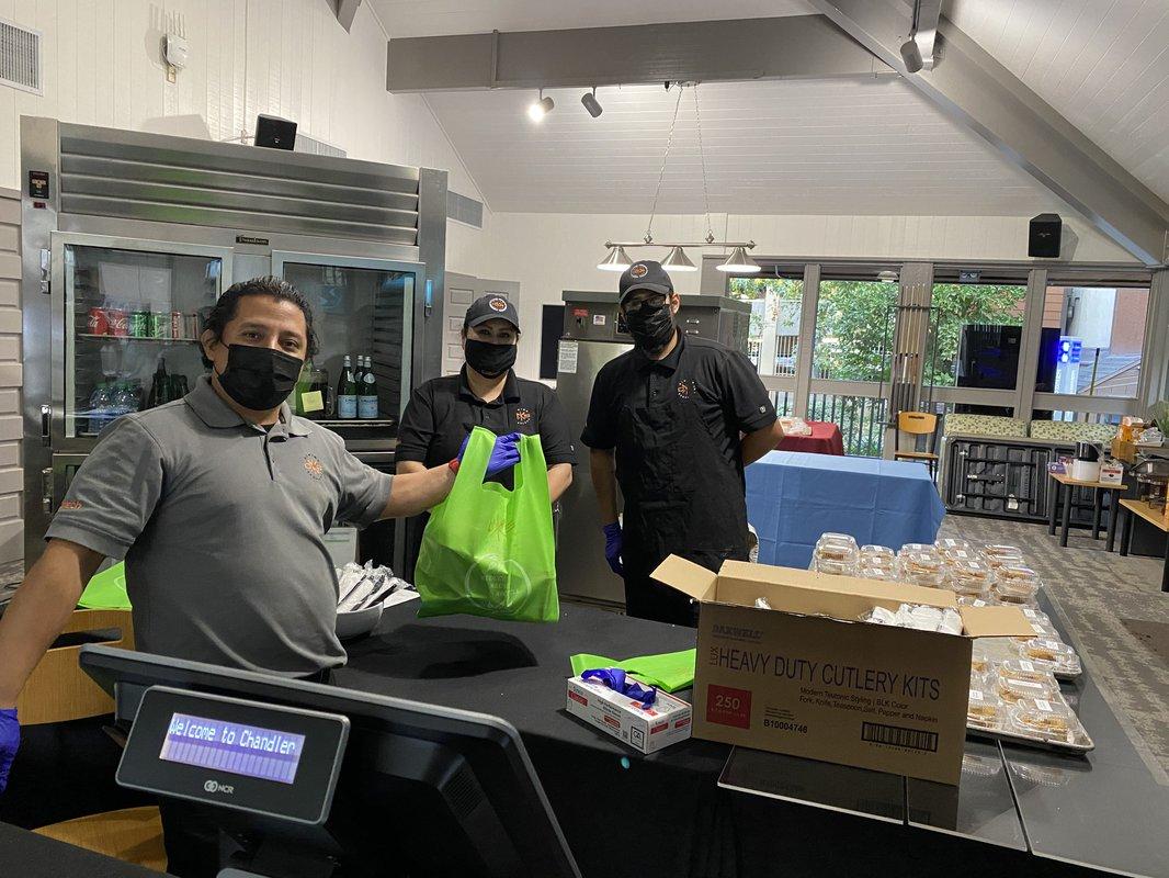 Three masked staffers prepare bags of food.
