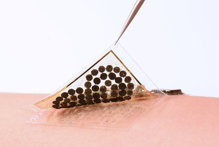 A pair of tweezers peels a sample of a electronic skin from the skin of an arm.
