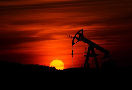 Oil derricks pump as the sun sets in the background
