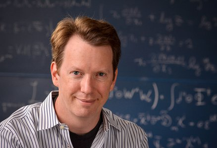 Headshot of Sean Carroll in striped shirt in front of a blackboard with equations