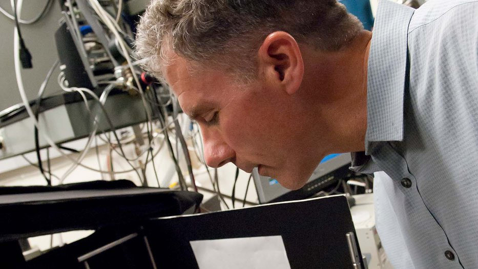 Man bending over scientific equipment using tweezers to adjust