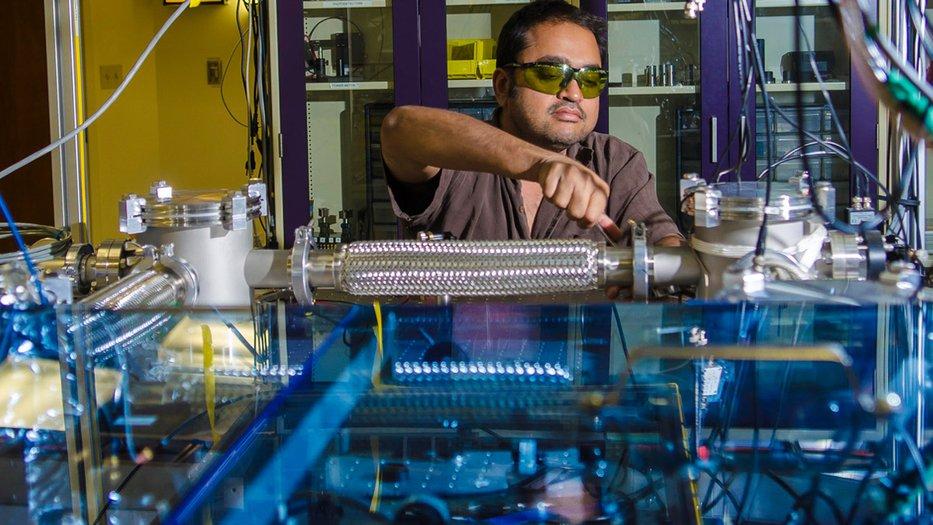 Photo of Rana Adhikari working in his lab