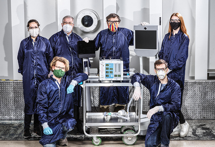 Members of the JPL team that created the prototype ventilator, pictured in masks with the prototype