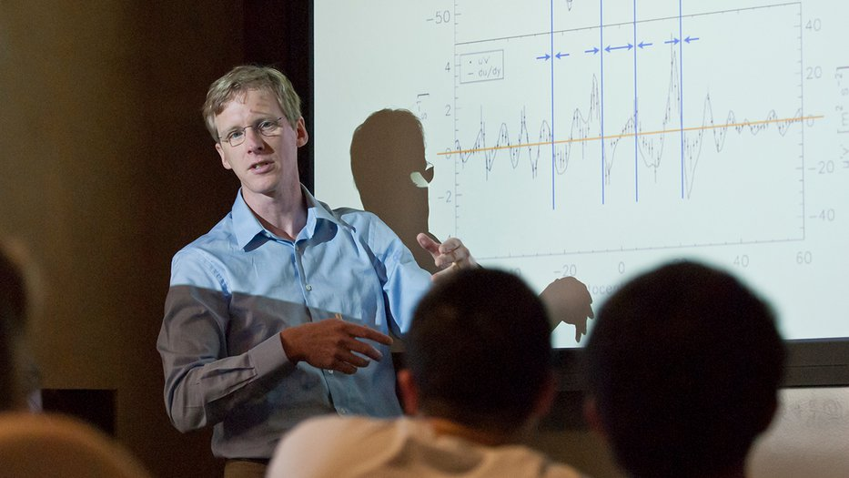 Professor Schneider teaching in front of a classroom with a graph behind him