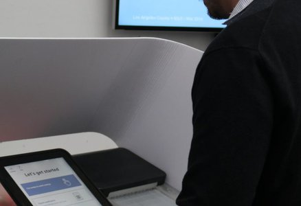 Man standing at electronic voting booth