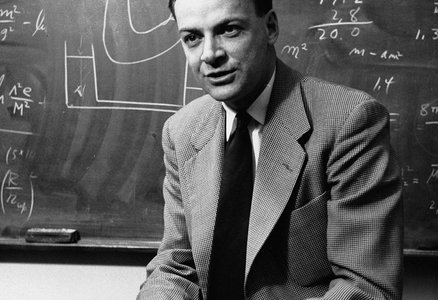 Richard Feynman sitting on a desk in front of a chalkboard with equations