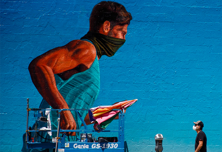 Photo of man in mask walking by mural of running person in neck gaiter