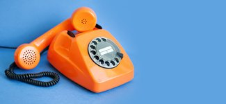 Orange telephone on blue background